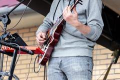 Händer av den unga musikern som spelar den electro gitarren under performanc arkivbild