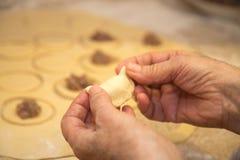 Händer av den vita äldre kvinnan att göra hemlagad klimpnärbild arkivfoton