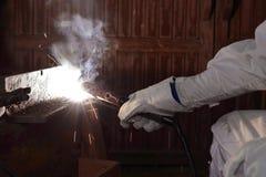 Händer av den yrkesmässiga industriella weldermannen med facklan och svetsningmetall för skyddande handskar stålsätter med gnista Royaltyfria Foton