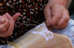 Händer av en äldre kvinna som broderar en snöra åt med tombolo och c Royaltyfri Fotografi