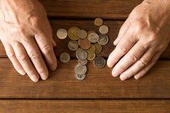 Händer av en äldre man med olika mynt på en trätabell Th arkivfoto