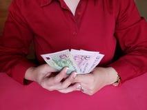 händer av en affärskvinna som rymmer singaporean sedlar arkivfoton