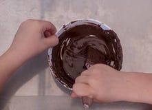 Händer av en barnlek den blandande chokladen för konditor i en bunke Arkivbild