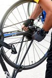 Händer av en cyklistnärbild som reparerar ett cykelhjul royaltyfri fotografi