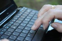 Händer av en dam av den höga åldern genom att använda en bärbar datordator Royaltyfri Fotografi