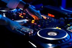 Händer av en discjockey som blandar musik på ett disko arkivbild
