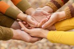 Händer av en familj tillsammans på höstbakgrund royaltyfri foto