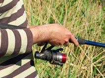 Händer av en fiskare med snurrstången på en flod. Arkivbilder
