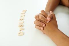 Händer av en flicka bildar orddyslexin Arkivbild