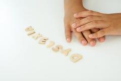 Händer av en flicka bildar orddyslexin Arkivfoton