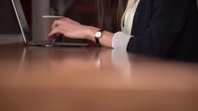 Händer av en flicka med klockamaskinskrivning på bärbar datortangentbordet med kaffe lager videofilmer