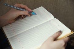 Händer av en flicka som skriver i en anteckningsbok Arkivfoto
