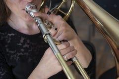 Händer av en flicka som spelar trombonen arkivfoton