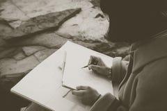 Händer av en flickateckning med blyertspennan arkivbild
