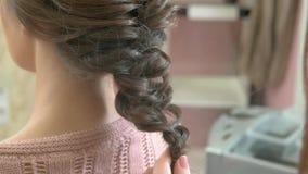 Händer av en frisör, flätad tråd