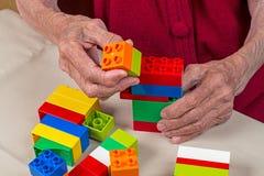 Händer av en gammal kvinna med plast- kvarter arkivfoton