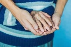 Händer av en gammal kvinna och en ung man Att bry sig för åldringen C Royaltyfri Foto