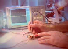 Händer av en hög manlig tekniker som testar elektronisk utrustning Arkivbild