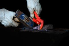 Händer av en hovslagare i hammare för w för vitläderhandskar blå och röd klämma under arbete royaltyfri foto