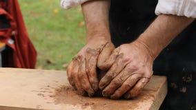 Händer av en keramikercloseup En klumpa sig av lera i händer för man` s stock video