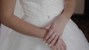 Händer av en kvinna i en vit klänning lager videofilmer