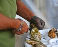Händer av en kvinna med den chain handsken och kniven som öppnar en ostron royaltyfri fotografi