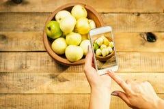 Händer av en kvinna som gör ett äpplefoto vid en smartphone Arkivfoto
