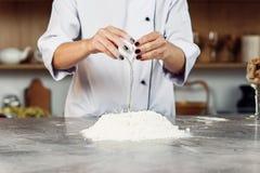 Händer av en kvinnlig kock som bryter ett ägg in i en hög av mätt mjöl, medan göra deg arkivfoto