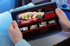 Händer av en man i en website av en servic restaurangmatleverans Royaltyfria Bilder