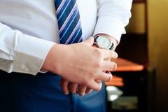 Händer av en man i en skjorta och bandet med ett klockaslut upp royaltyfria bilder