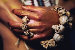 Händer av en man med ett armband av skallar arkivbilder