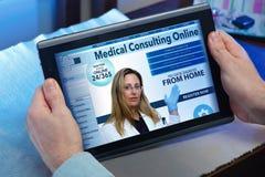 Händer av en man på en website av online-hälsovård i tablen Arkivbild