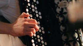 Händer av en man som spelar dragspelet på en konsert lager videofilmer