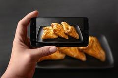 Händer av en man tar foto av mat på tabellen med telefonen Nya bullar med grönsakfyllning Vetebröd som fyller på ett mörker arkivfoton