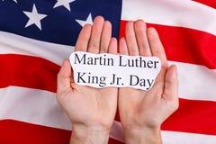 Händer av en manhåll inskriften är Martin Luther King Jr Dag mot bakgrunden av amerikanska flaggan royaltyfri foto