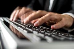 Händer av en manmaskinskrivning fastar på ett datortangentbord royaltyfria bilder