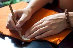 Händer av en modeformgivare på arbete med torkduken arkivbild