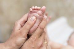 Händer av en moder som masserar hennes babys fot Royaltyfri Bild