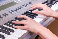 Händer av en ung flicka bredvid pianotangenterna Flickan spelar royaltyfri foto