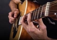 Händer av en ung grabb som spelar gitarren Arkivfoton