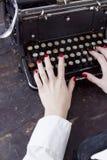 Händer av en ung kvinna skrivev ut på en skrivmaskin Royaltyfria Foton