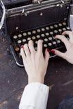 Händer av en ung kvinna skrivev ut på en skrivmaskin Arkivfoto
