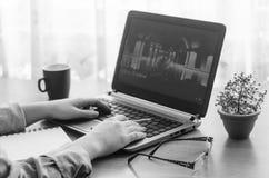 Händer av en ung kvinna som arbetar bak en bärbar dator Royaltyfria Foton