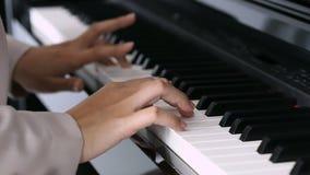 Händer av en ung kvinna som spelar pianot stock video