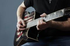 Händer av en ung man som spelar en gitarr med en amerikan Arkivbild