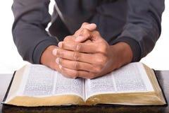 Händer av en ung man vek att be över en bibel, händer över den mjuka fokusbibeln royaltyfri bild