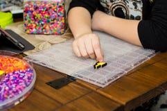 Händer av en unge som förlägger pärlor på ett pinnebräde för ett tillverka projekt Arkivbild