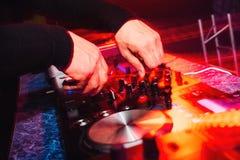 Händer av en yrkesmässig discjockey som spelar och blandar musik med ljusa ljusa effekter Arkivfoto