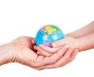 Händer av ett barn och ett hållande jordklot för man Royaltyfria Bilder