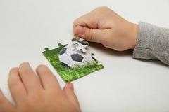 Händer av ett barn sammanställer ett pussel med en fotbollboll arkivbild